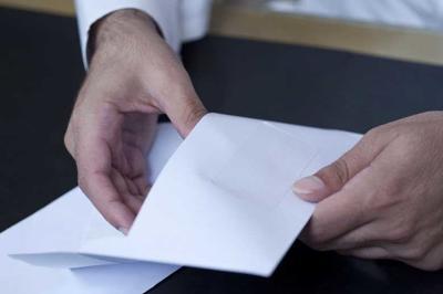 Businessman hands opening an envelpoe