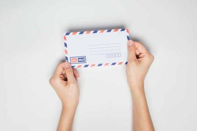 A female(woman) hand hold a envelope isolated white at the studio.