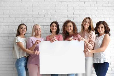 Women wearing silk ribbons holding poster with space for text against brick wall. Breast cancer awareness concept