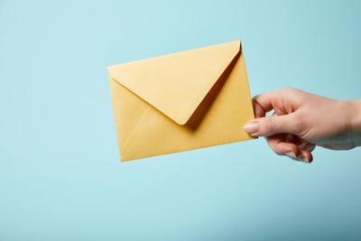 cropped view of woman holding bright and yellow envelope on blue background