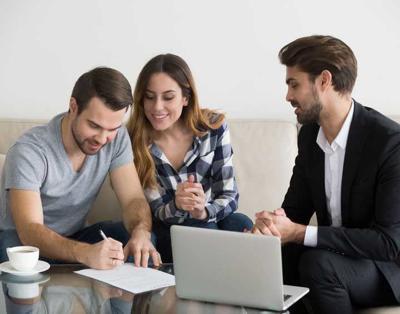Happy couple renters or tenants sign rental contract meeting realtor