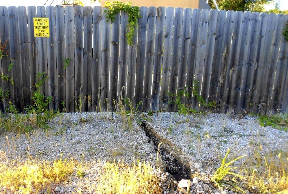 Trench From Rapidly Flowing Sewage Under The Fence