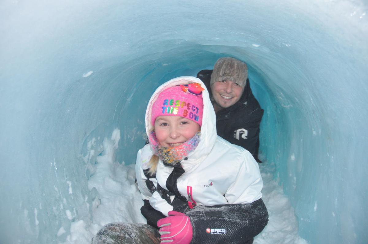 Adalyn Corwin, 9, and her father, Keith Corwin, complete their crawl through an ice castle tunnel