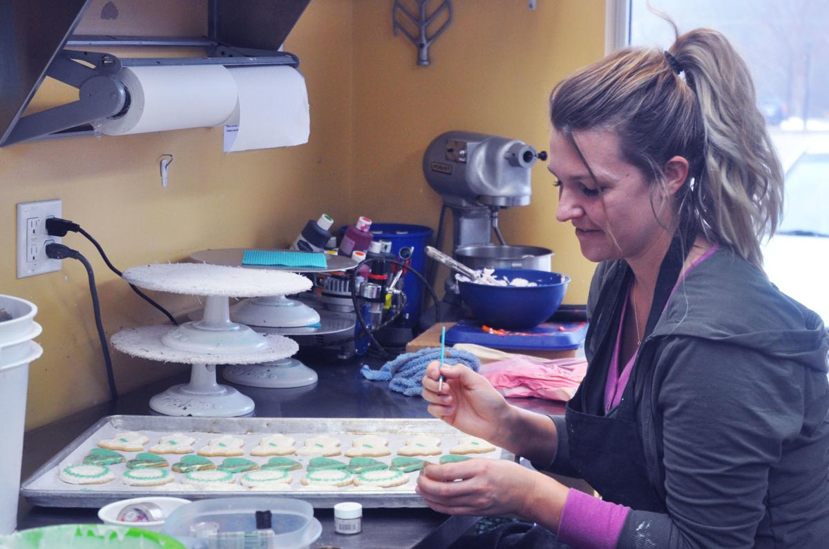 Abby Miller, Lorelei Bittner's Bakery employee, decorates some cookies