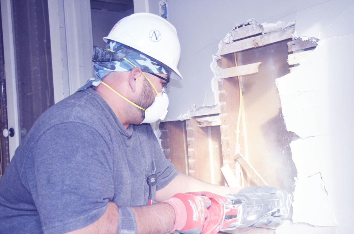 James Clendening, Nikao Group employee, drills some walls in the Brick & Mortar building