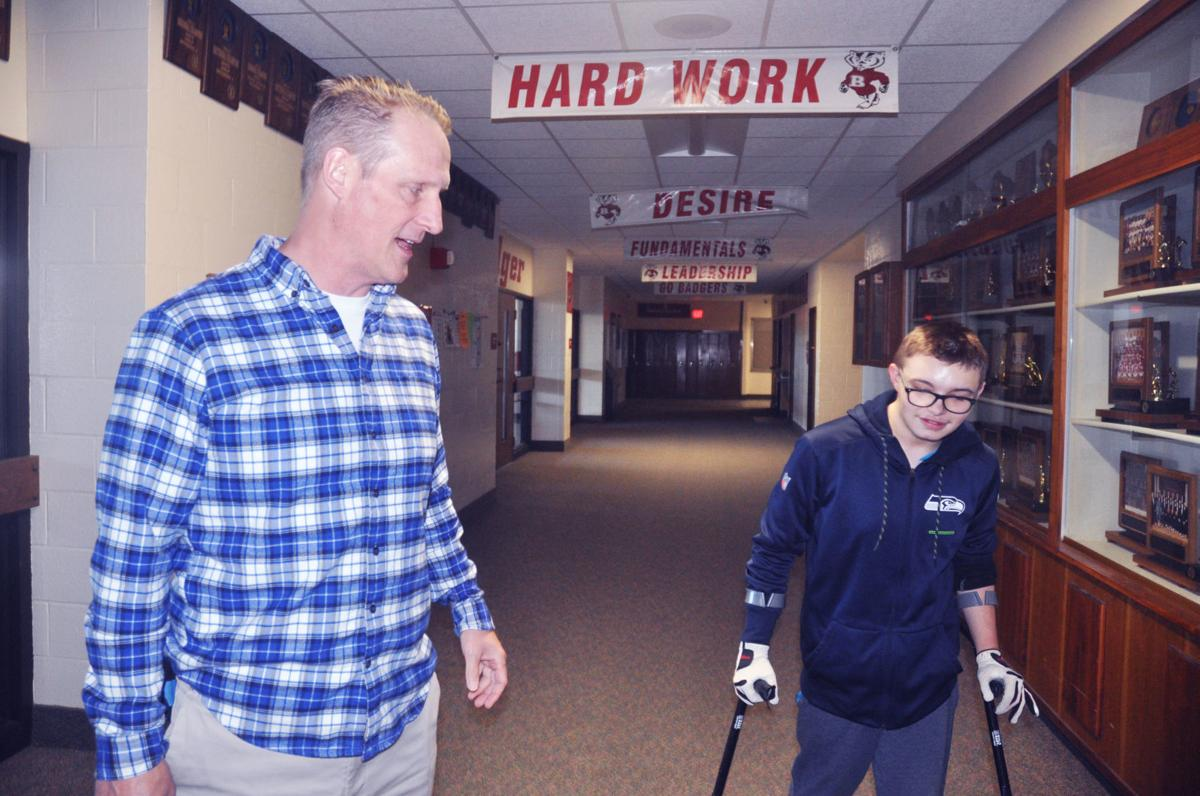 Assistant Principal Michael Giovingo, left, and Brooks Guif, junior, walk down the hallway