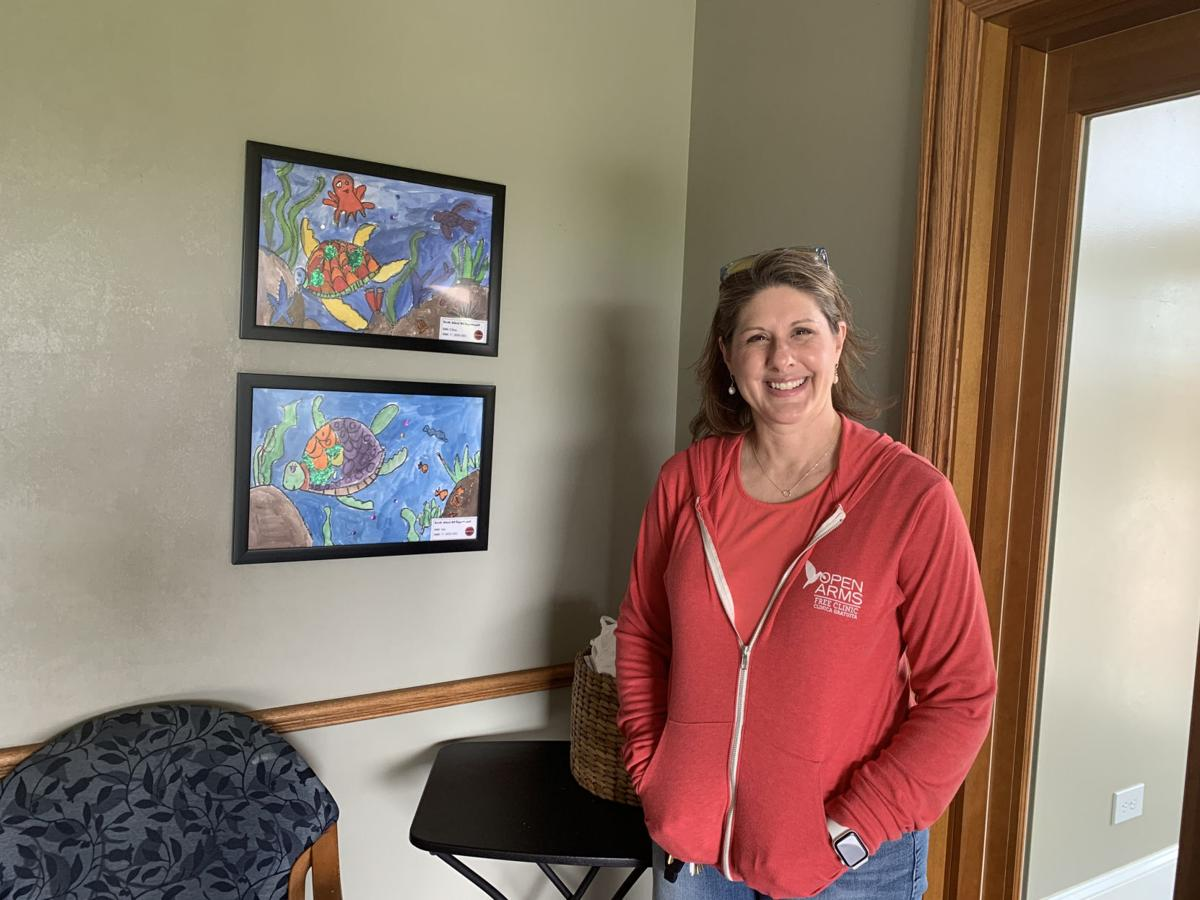 Sara Nichols, executive director for the Open Arms Free Clinic in Elkhorn, stands next to some artwork in the clinic's dental care facility that were donated by several Woods Elementary School students