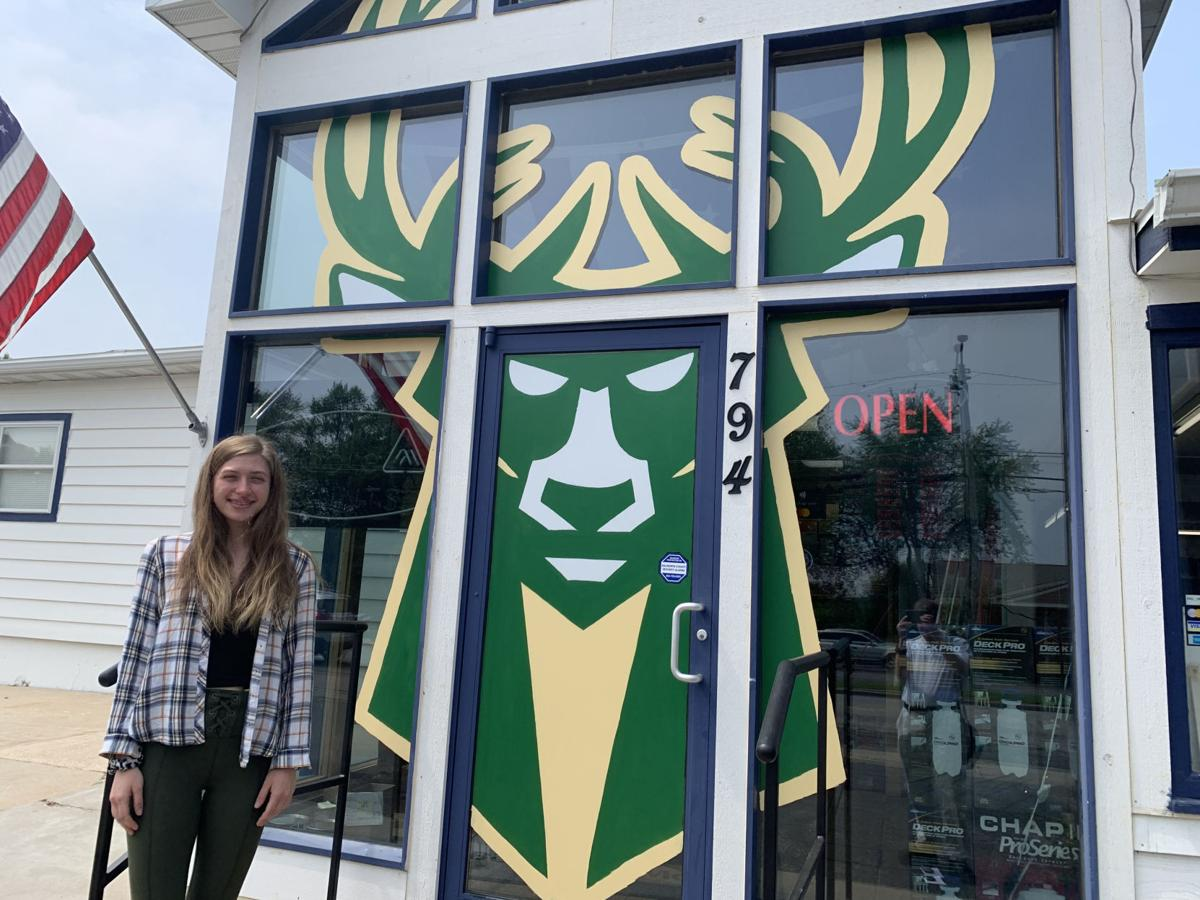 Tara Laine, employee at Geneva Paint & Decorating, recently painted a Milwaukee Bucks logo on the business's front glass door