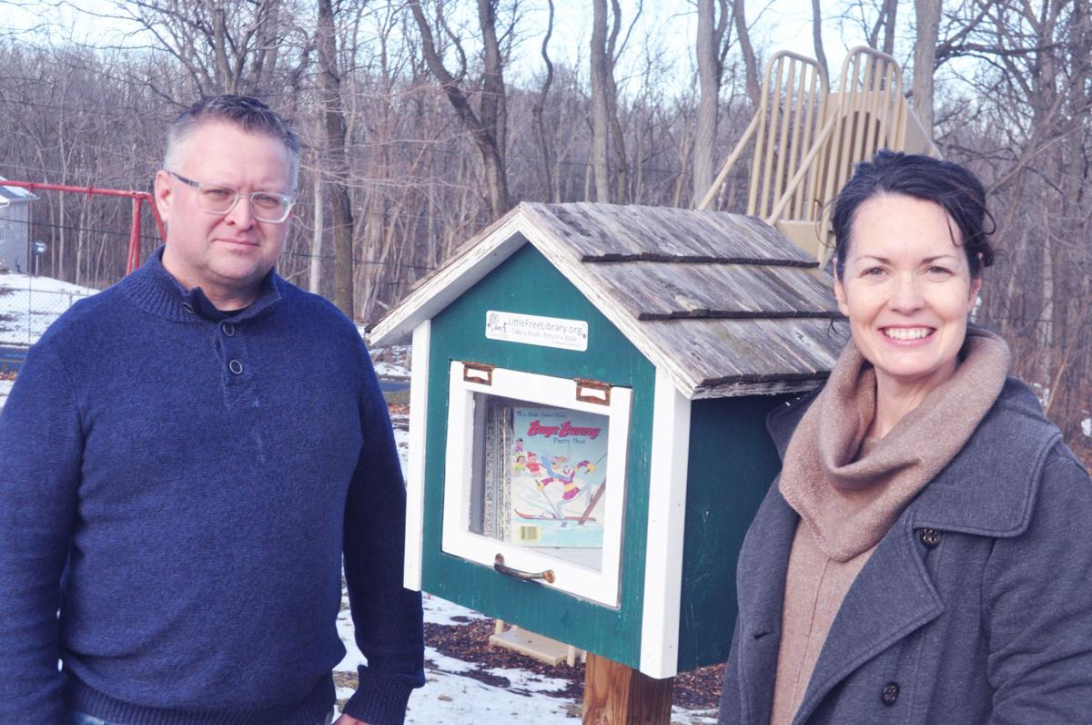 Nils and Teresa Haldorsen of Lake Geneva stand next to a Little Free Library in West Gate Top Tot Park that their son