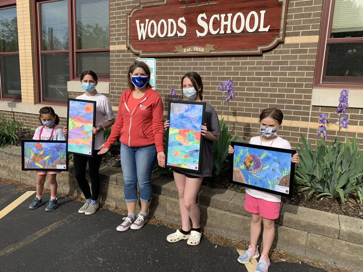 A group of Woods Elementary School students donate some paintings to Open Arms Free Clinic