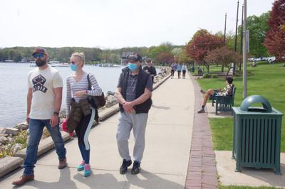 Visitors wear face masks in Library Park in Lake Geneva