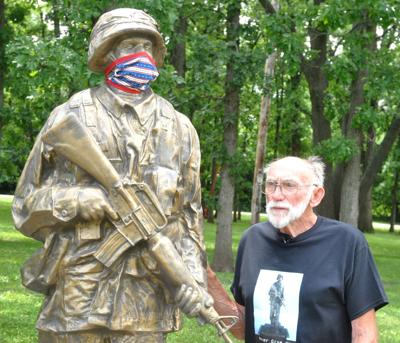 Richard Olenoski looks over a military statue that he and other Bloomfield residents help bring