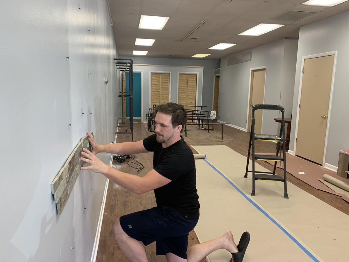 Tyler Dempsey, owner of Holistic Connections, prepares to install a rock wall