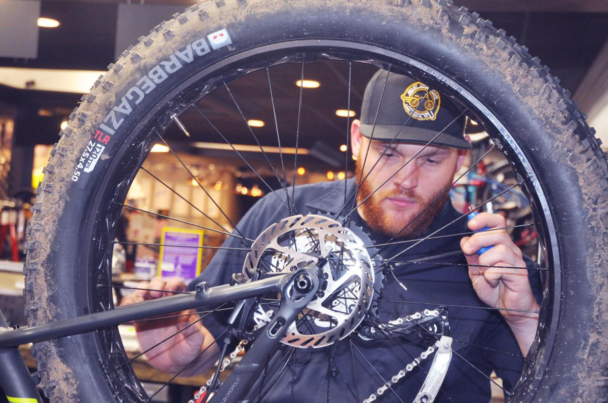 Michael Winters, Avant Cycle Cafe employee, repairs a bicycle