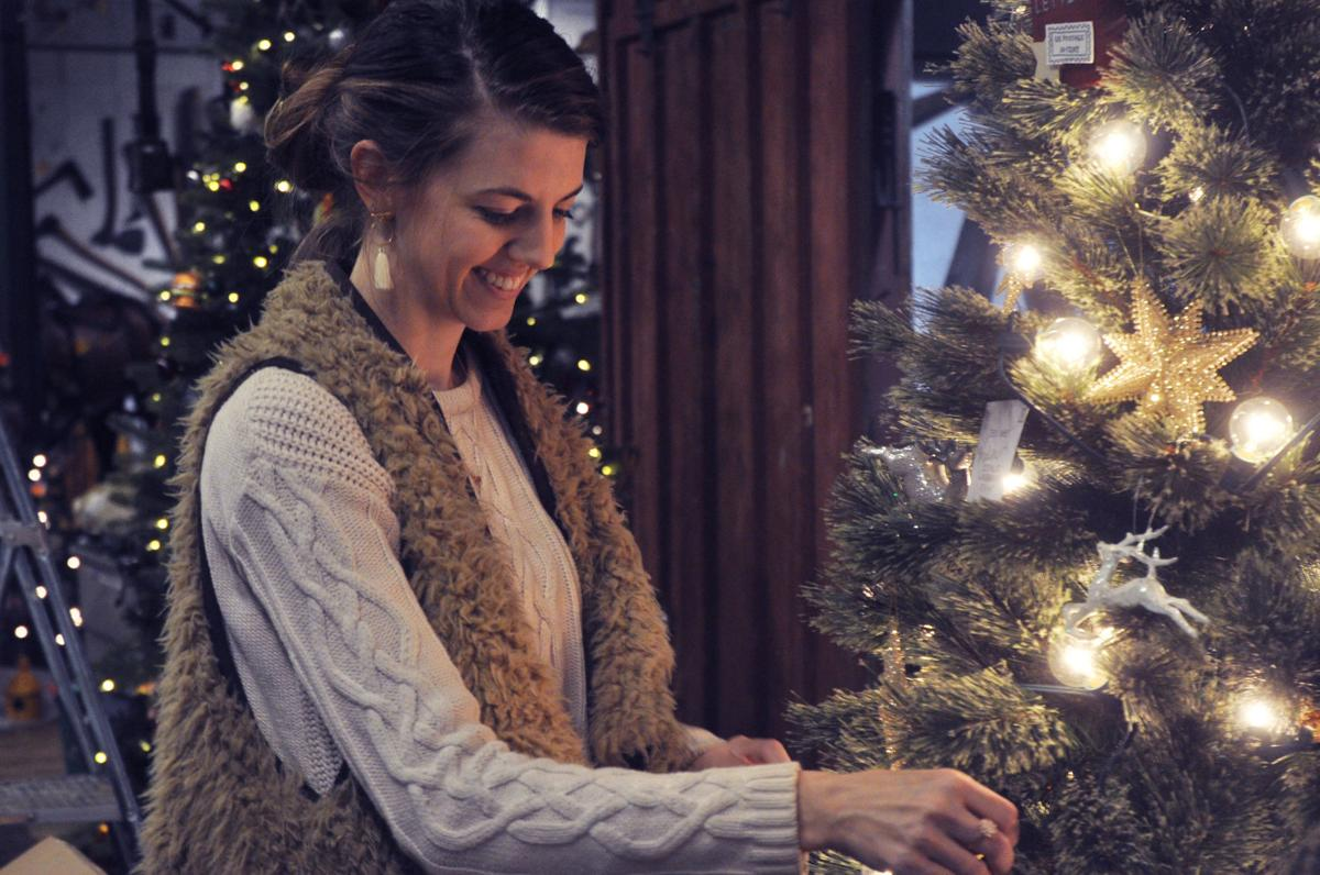 Felicia Belch, co-owner of Deerly Detailed Events, is all smiles as she decorates a Christmas tree