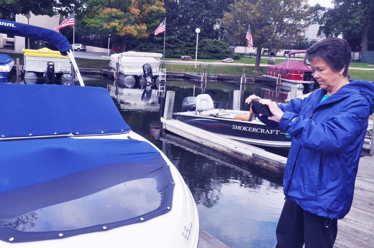 Harbormaster Linda Frame takes photographs of a boat cover that has been covered with water