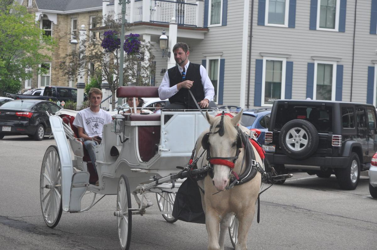 Richard Costa drives passengers on a horse-drawn carriage in Lake Geneva's Maple Park Historic District