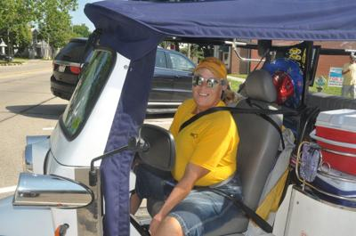 Cyndy Hansen, owner of Cruzin' Taxi Transportation, demonstrates one of the tuks that she plans to use as part of a ride service