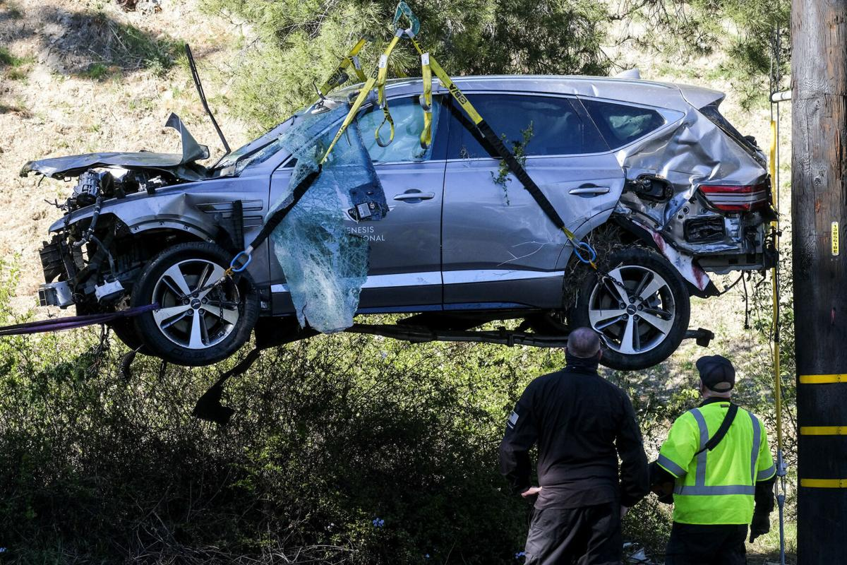 Workers watch as a crane is used to lift a vehicle following a rollover accident involving golfer Tiger Woods, Tuesday, Feb. 23, 2021, in the Rancho Palos Verdes section of Los Angeles.