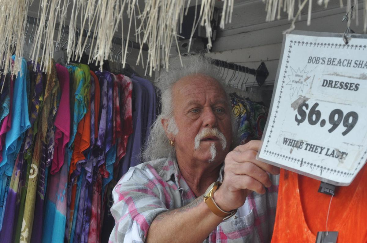 Bob Lee, owner of Bob's Beach Shack, arranges items outside his store