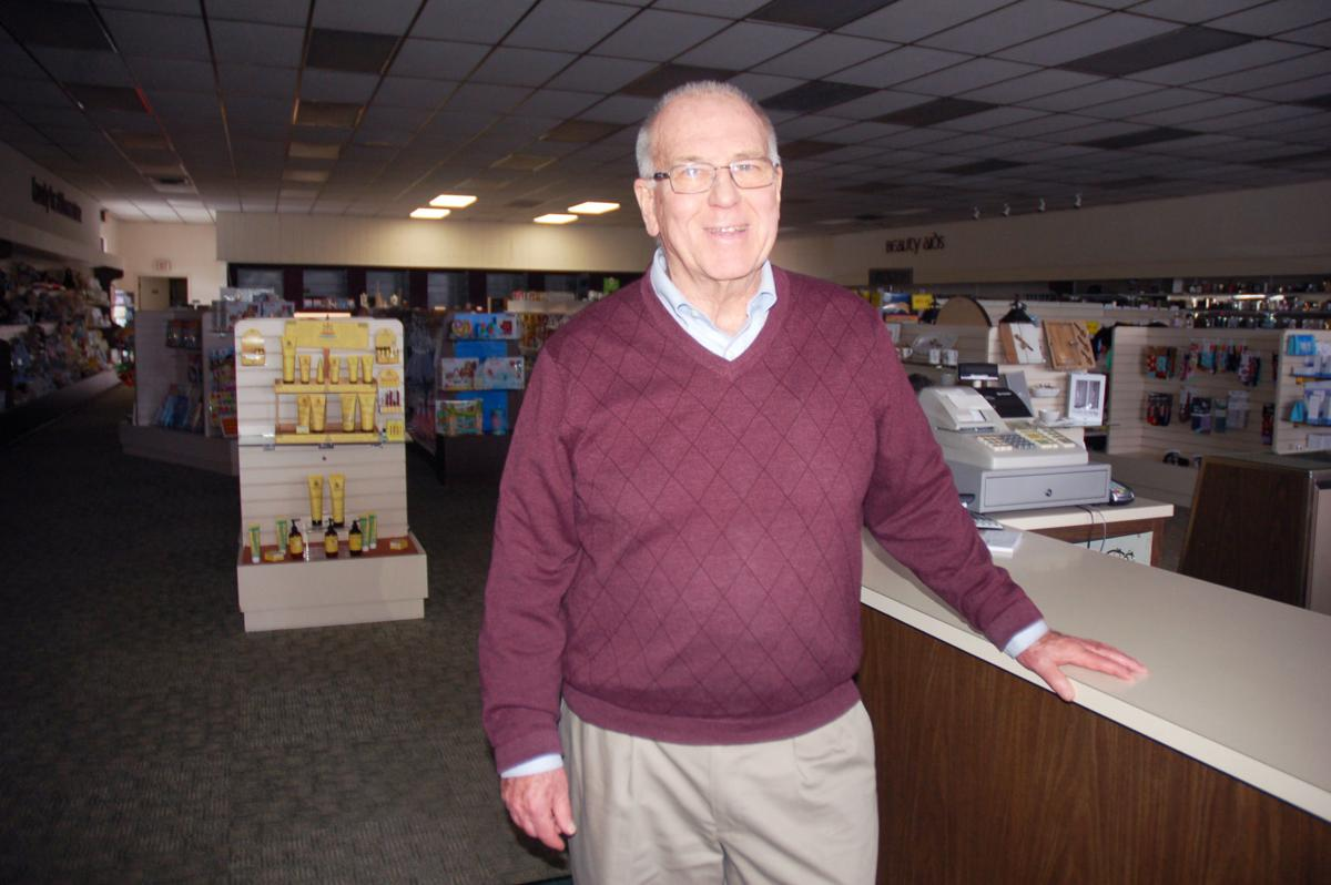 Jim McCullough at counter of Walworth store closing March 2020