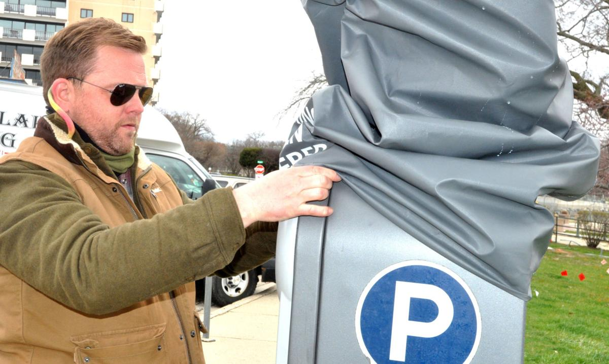 Seth Elder, parking operations manager, performs some maintenance to a parking kiosk