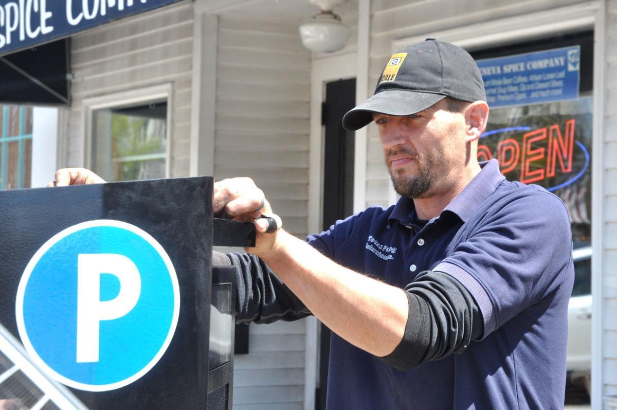 Nick Sondelski of Total Parking Solutions checks over a parking kiosk