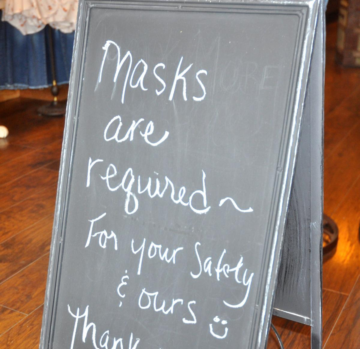 A sign posted near the Twelfth & Brown store requires customers to wear facemasks before entering