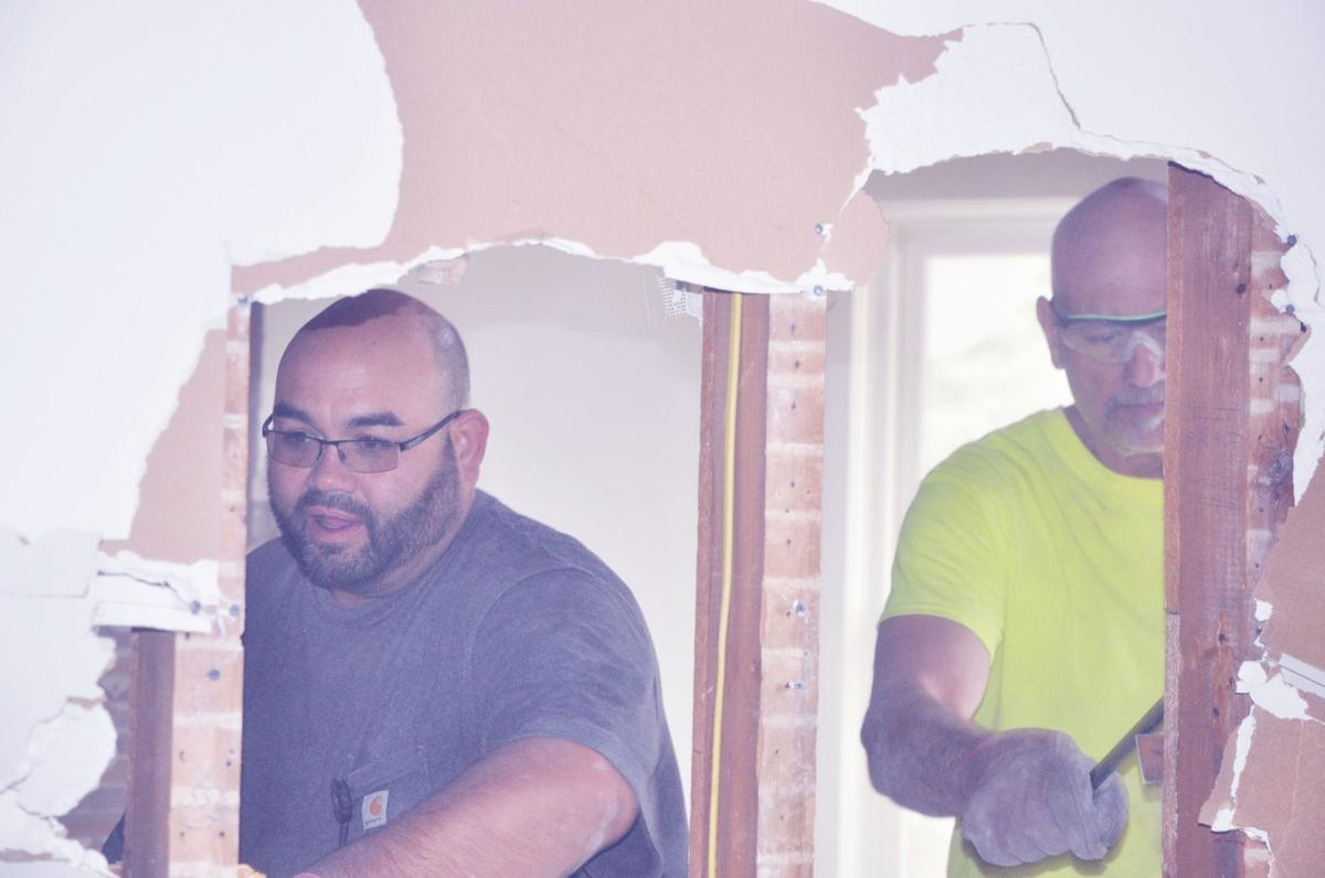 James Clendening and Edward Holzman, Nikao Group employees, tear down some walls