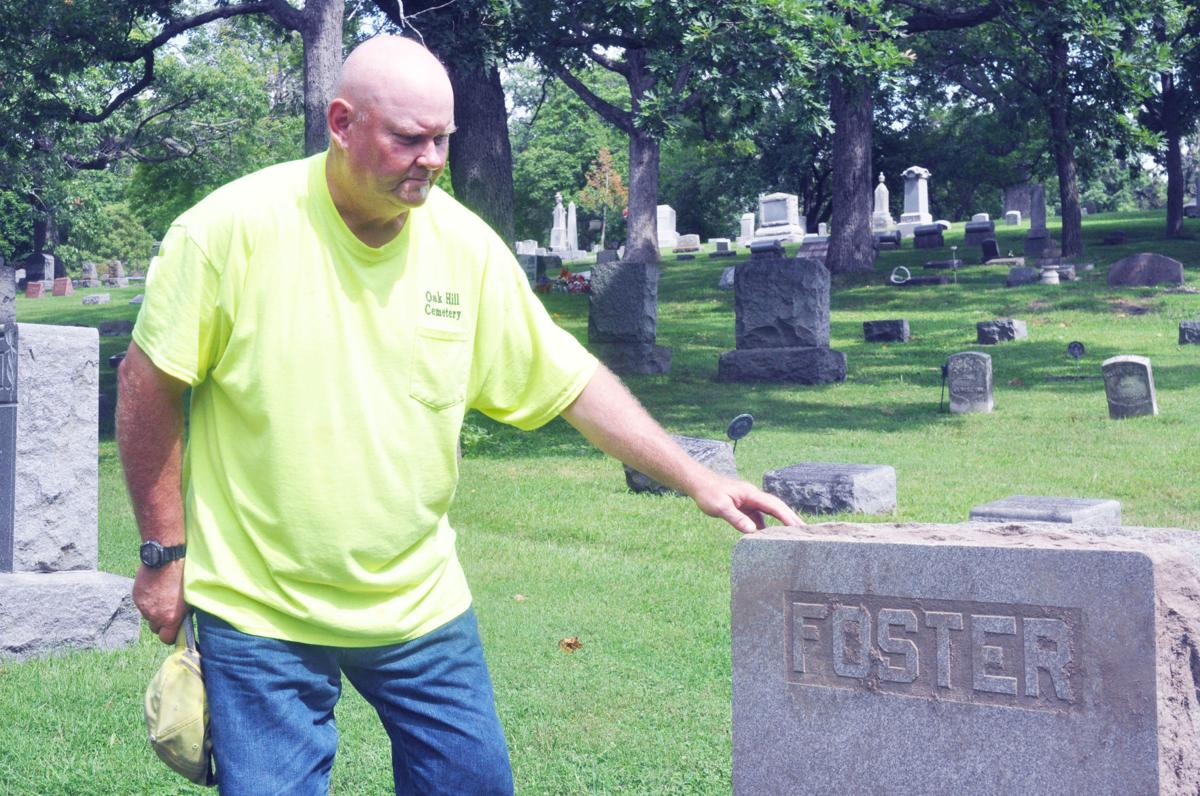 Clint Melancon, Oak Hill Cemetery superintendent, looks over a headstone that has been restored