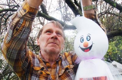 Patrick Macara of Walworth hangs Halloween decorations