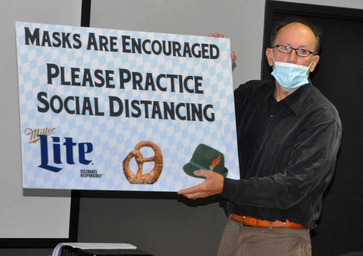 Spyro Condos, president of the Lake Geneva Business Improvement District Board, holds up a sign