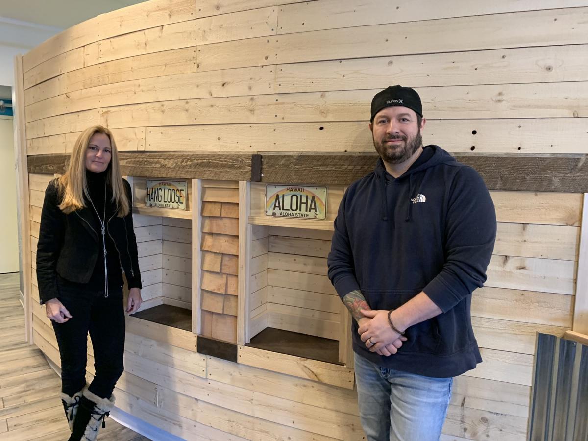 Karen Schutz and Joshua Bernicchi stand next to renovated space at Wicked Poke Hut