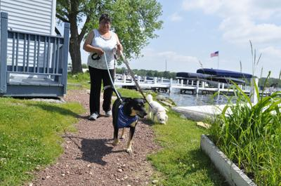 Mercy Stevenson with dogs on lake shore path