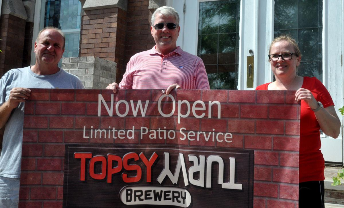 Terry Remke, sales manager, Daniel Schuld, and Tina O'Malley hold up a sign