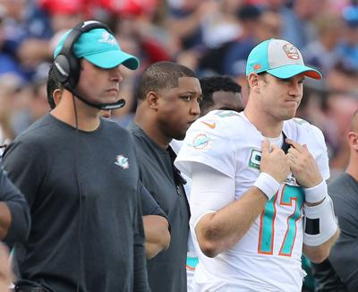 Miami Dolphins coach Adam Gase and quarterback Ryan Tannehill watch back up quarterback Brock Osweiler in the fourth quarter as they play the New England Patriots on Sunday, Sept. 30, 2018 at Gillette Stadium in Foxborough, Mass.