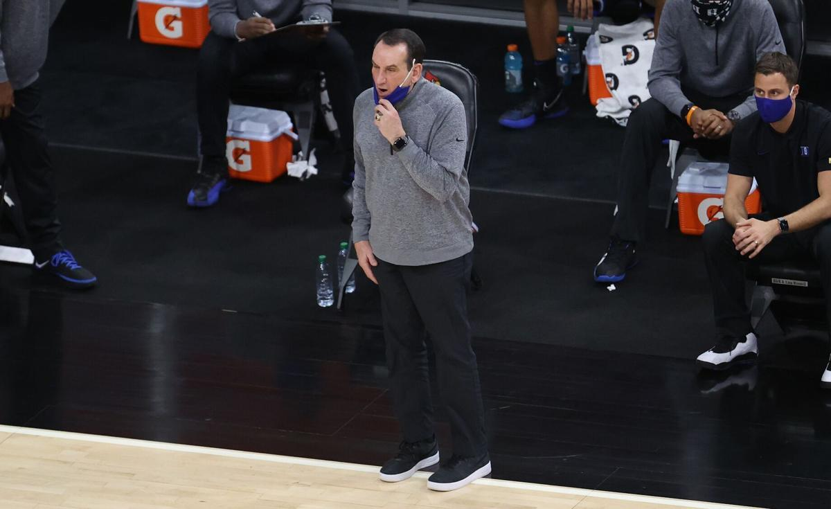 Mike Krzyzewski, head coach of the Duke Blue Devils, gives instructions to his team against the Louisville Cardinals at KFC YUM!