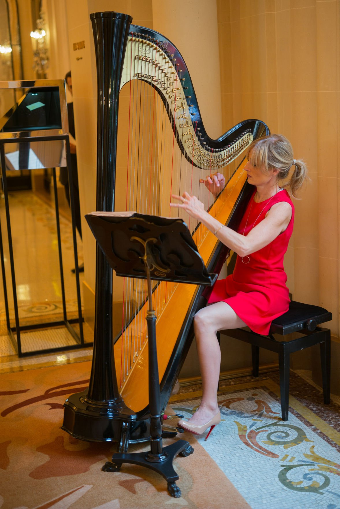 Hotel Plaza Athenee harpist plays inside La Galarie in the hotel lobby.