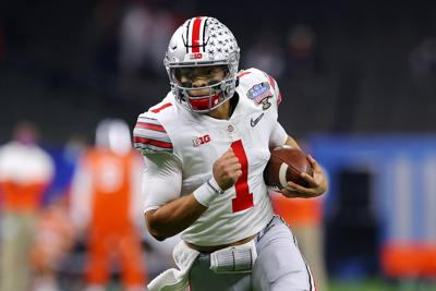 Ohio State quarterback Justin Fields runs with the ball in the first half against Clemson during the College Football Playoff semifinal game at the Allstate Sugar Bowl at Mercedes-Benz Superdome in New Orleans on Jan. 1, 2021.