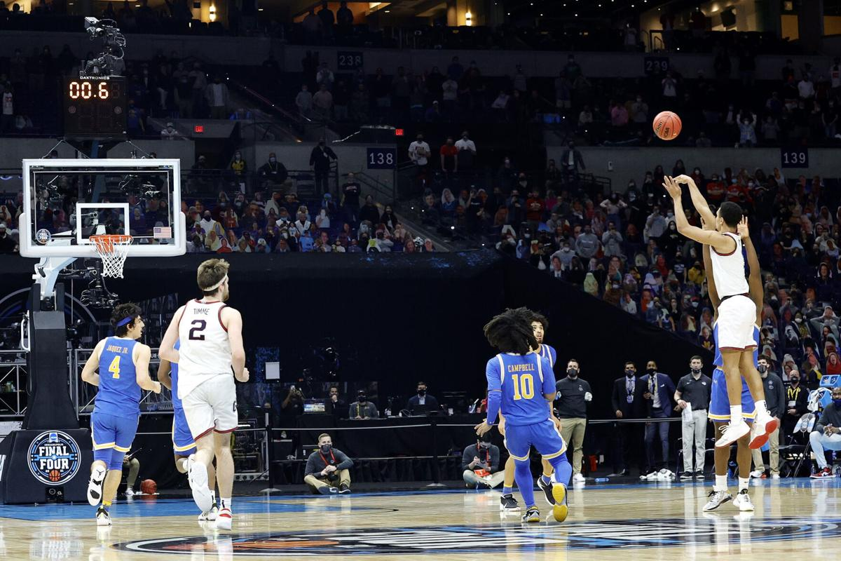 Jalen Suggs of the Gonzaga Bulldogs shoots a game-winning three-point basket in overtime to defeat the UCLA Bruins 93-90 during the 2021 NCAA Final Four semifinal at Lucas Oil Stadium on April 03, 2021 in Indianapolis, Indiana.