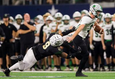 Southlake Carroll quarterback Quinn Ewers is pulled down by DeSoto linebacker Ridarius Branch during the second quarter of a Class 6 A Division I area-round high school football playoff game between Southlake Carroll and DeSoto on Friday, November 22, 2019 at AT&T Stadium in Arlington.