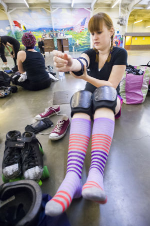 Reporter Skates After Her Derby Girl Dreams : News-Sentinel reporter Sara Jane Pohlman straps on pads before taking to the rink with the Port City Roller Girls roller derby team at the San Joaquin County Fairgrounds on Thursday, Feb. 7, 2013.  - Dan Evans/News-Sentinel