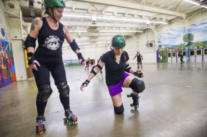 """Reporter Skates After Her Derby Girl Dreams : With instruction from """"Malice,"""" left, of the Port City Roller Girls roller derby team, News-Sentinel reporter Sara Jane Pohlman stands without using her hands after falling.  - Dan Evans/News-Sentinel"""