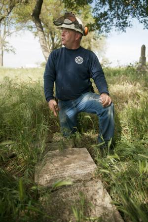 Galt firefighter Eric Schneider works to clean up historic cemetery