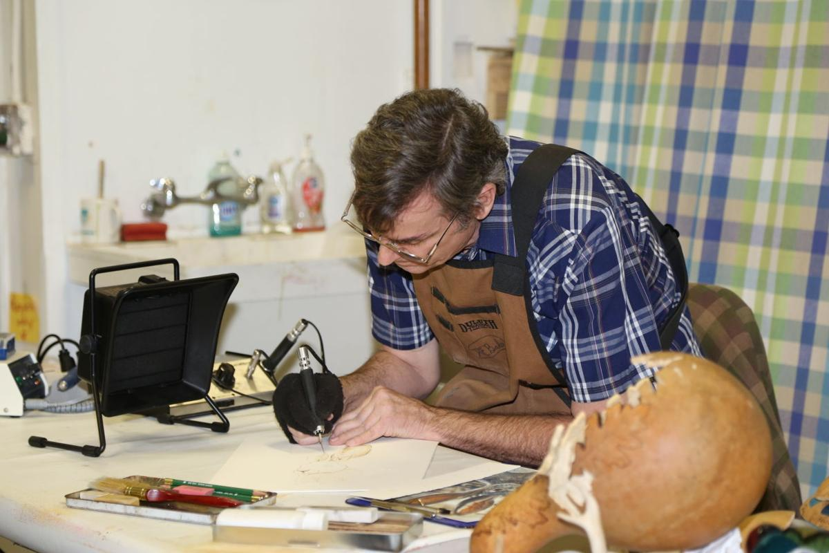 Artist Eric Baker uses flames and knives to alter gourds at Lodi Community Art Center