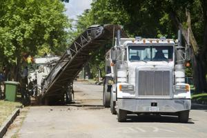 Asphalt grinder tears up road for water main project