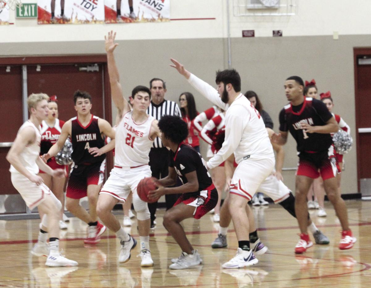 Boys basketball: Flames torched by Trojans
