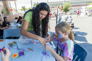 Little Buckaroos Saddle Up To Read At The Reading Roundup : Stefany Lima, left, helps Clair Selling, 9, to make popsicle stick crafts during the second annual Little Buckaroos Reading Roundup Literacy Fair, hosted by the Lodi News-Sentinel and the Lodi Public Library, on Locust Street in Downtown Lodi on Saturday, Aug. 24, 2013. - Ian Jonsson/News-Sentinel