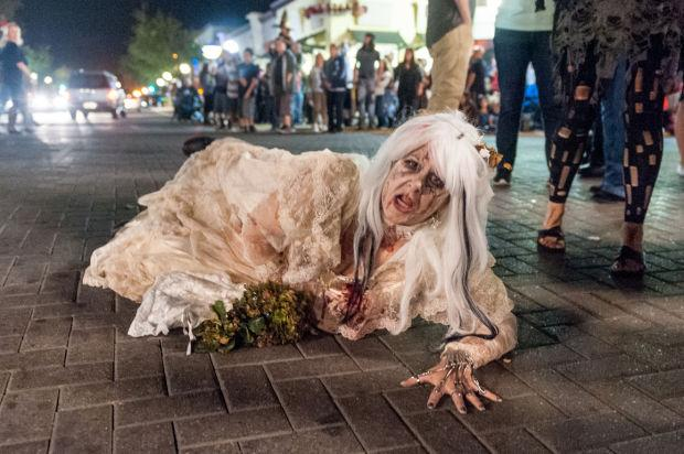 "<p>Amber Schmidig crawls in the street during Downtown Lodi's fourth annual Zombie Walk on Saturday, Oct. 26, 2013. Crowds gathered at Take 27, across School Street from the Lodi Stadium 12 movie theater, at 6 p.m. to get their makeup done. Later, participants enjoyed a screening of ""Beetlejuice"" at the movie theater.</p>"
