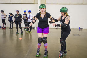 """Reporter Skates After Her Derby Girl Dreams : """"Malice,"""" right, helps News-Sentinel reporter Sara Jane Pohlman balance while practicing stops.  - Dan Evans/News-Sentinel"""